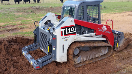 The Takeuchi TL10 Compact Track Loader using its ripper bar to break up a compacted surface.