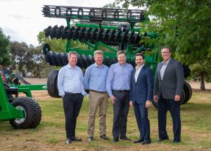 5 men behind them a tractor